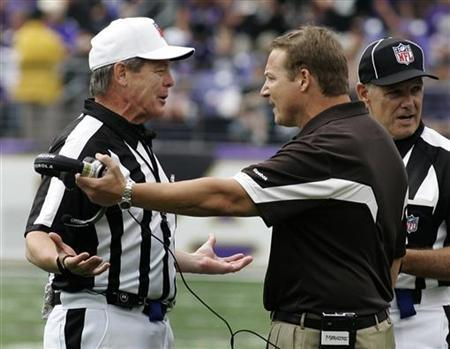 Cleveland Browns head coach Eric Mangini (C) speaks with referee Scott Green (L) as side judge Larry Rose looks away during the third quarter of the Browns' NFL game against the Baltimore Ravens in Baltimore, Maryland September 26, 2010. REUTERS/Joe Giza