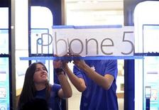 Apple employees hang an iPhone 5 sign at one of the company's retail locations shortly before sales began in San Francisco, California, September 21, 2012. REUTERS/Noah Berger