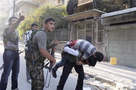 A member of the Free Syrian Army carries his wounded comrade who was shot during clashes with the Syrian Army forces as others shout for help in Aleppo September 27, 2012. REUTERS/ Zain Karam