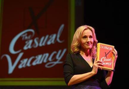 Author J.K Rowling poses for photographers with a copy of her adult fiction book ''The Casual Vacancy'', at the Queen Elizabeth Hall in London September 27, 2012. REUTERS/Paul Hackett