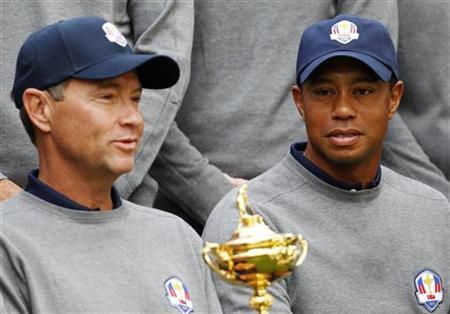 U.S. golfer Tiger Woods (R) looks at the Ryder Cup as it is held by captain Davis Love III during the 39th Ryder Cup golf matches at the Medinah Country Club in Medinah, Illinois, September 25, 2012. REUTERS/Matt Sullivan