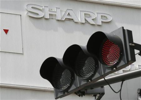 Sharp's logo is seen behind a traffic sign outside an electronics shop in Tokyo September 7, 2012. REUTERS/Kim Kyung-Hoon
