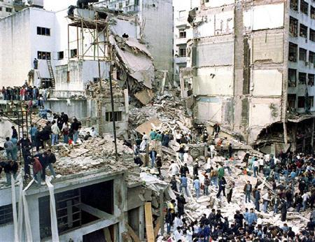 Rescue workers search for survivors and victims in the rubble left after a powerful car bomb destroyed the Buenos Aires headquarters of the Argentine Israeli Mutual Association (AMIA), killing 85 people, in this July 18, 1994 file photo. REUTERS/Enrique Marcarian/Files