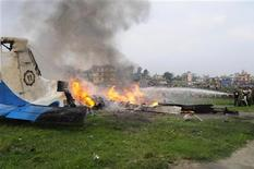 Спасатели тушат огонь на обломках разбившегося в Катманду самолета, 28 сентября 2012 года. Падение небольшого самолета почти сразу после вылета из столицы Непала Катманду унесло жизни 19 человек, включая семерых граждан Великобритании и пяти граждан КНР, сообщили представители авиакомпании, которой принадлежало воздушное судно. REUTERS/STRINGER
