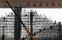 Workmen stand on scaffolding underneath a railway bridge located on the outskirts of Beijing September 13, 2012. REUTERS/David Gray