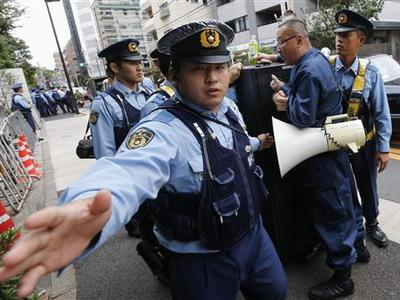 A policeman gestures at a photographer to stop taking pictures as he and other police officers block a protester shouting anti-China slogans in front of the Chinese Embassy in Tokyo September 28, 2012. REUTERS/Kim Kyung-Hoon