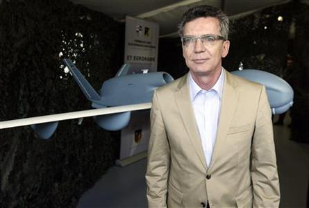 German Defence Minister Thomas de Maiziere stands in front of a model of the 'EuroHawk' unmanned aerial vehicle (UAV) during his visit to the Joint Support Service base in Grafschaft near the western German city of Bonn, in this file picture taken July 12, 2011. REUTERS-Wolfgang Rattay-Files