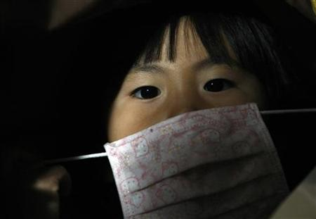 A passenger wearing a face mask arrives at Narita international airport on a direct flight from Mexico, in Narita April 29, 2009. REUTERS/Issei Kato/Files