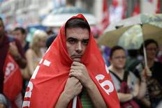 A protester covers himself with a CGIL union flag during a rally in downtown Rome September 28, 2012. Two of Italy's biggest unions marched through Rome on Friday to protest against Prime Minister Mario Monti's cuts in public spending as opposition grows to austerity policies aimed at steering the country out of its economic crisis. REUTERS/Tony Gentile