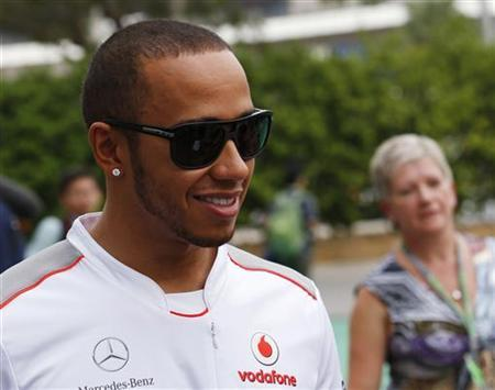 McLaren Formula One driver Lewis Hamilton of Britain arrives at the paddock with his mother Carmen Lockhart (background R), ahead of the Singapore F1 Grand Prix at the Marina Bay street circuit in Singapore September 23, 2012. REUTERS/Edgar Su