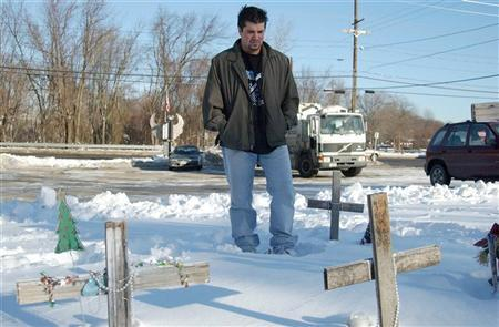 Station Night Club fire survivor Mike Ricardi, 20, of Worcester, Massachusetts, stands in front of a cross placed as a shrine to his friend Jim Gahen, who perished along with 99 others in the February 20, 2003 Station Night Club fire, December 9, 2003 in West Warwick, Rhode Island. REUTERS/Jessica Rinaldi