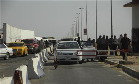 People wait at a security checkpoint as they enter the city of Tikrit, 150 km (93 miles) north of Baghdad, September 28, 2012. Dozens of prisoners, including convicted al Qaeda members, escaped from a jail in Tikrit after militants dressed in police uniform attacked the prison and released them, security sources said on Friday. REUTERS/Bakr al-Azzawi