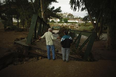 Two men speak to each other as they stand in front of a bridge destroyed by floodwaters in Alora, near Malaga southern Spain September 28, 2012. REUTERS/Jon Nazca