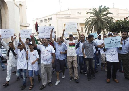 Demonstrators hold placards during a protest against the presence of militias and in support of the formation of a national army and police at Algeria Square in Tripoli September 28, 2012. REUTERS/Ismail Zitouny