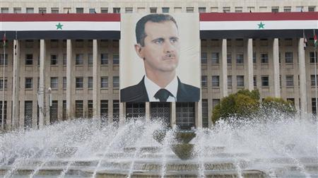 The picture of the Syria's President Bashar al-Assad is seen on central bank building in Damascus February 24, 2012. REUTERS/Khaled al-Hariri