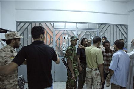 Security forces stand guard outside a building that was attacked by a crowd of protesters in Benghazi September 28, 2012. REUTERS/Stringer
