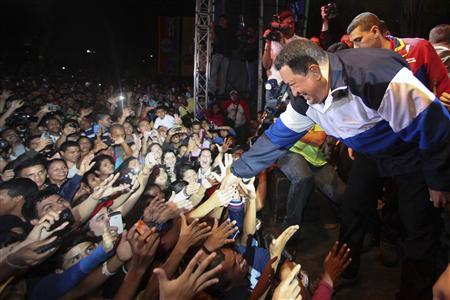 Venezuela's President and presidential candidate Hugo Chavez shakes hands with supporters in Caracas September 28, 2012. REUTERS/Miraflores Palace/Handout