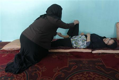 Muzhgan Masoomi, 22, exercises with the help of her doctor at her house in Kabul August 28, 2012. REUTERS/Omar Sobhani
