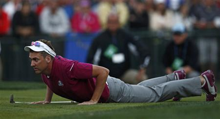 Team Europe golfer Ian Poulter of England lays on the ground to line up a putt on the 18th green during the afternoon four-ball round at the 39th Ryder Cup golf matches at the Medinah Country Club in Medinah, Illinois, September 29, 2012. REUTERS/Jim Young