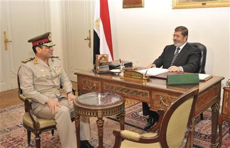 Egypt's President Mohamed Mursi (R) meets with Defence Minister General Abdel Fattah al-Sisi in Cairo August 22, 2012. REUTERS/Egyptian Presidency/Handout
