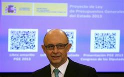 Spain's Treasury Minister Cristobal Montoro stands in front of a screen showing a document with a Quick Response (QR) code, representing the first draft of Spain's 2013 budget,during a ceremony at Parliament September 29, 2012. REUTERS/Sergio Perez