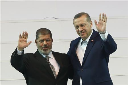 Turkey's Prime Minister and leader of ruling Justice and Development Party (AKP) Tayyip Erdogan (R) and his guest, Egypt's President Mohamed Mursi greet the audience during the AKP congress in Ankara September 30, 2012. REUTERS-Murad Sezer