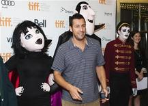 "Actor Adam Sandler poses with mascots of characters from ""Hotel Transylvania"", as he arrives on the red carpet for the film's gala presentation at the 37th Toronto International Film Festival, September 8, 2012. REUTERS/Mark Blinch"