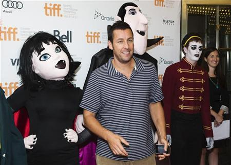 Actor Adam Sandler poses with mascots of characters from ''Hotel Transylvania'', as he arrives on the red carpet for the film's gala presentation at the 37th Toronto International Film Festival, September 8, 2012. REUTERS/Mark Blinch