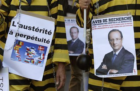 Protesters march through the streets of Paris during a demonstration against austerity plans, September 30, 2012. The placards read: ''Austerity, life sentence'' (L) and ''Wanted to be accountable for democratically'' (R). REUTERS/Christian Hartmann