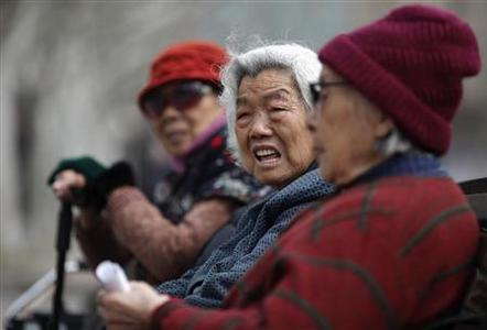 Women sit on a bench at a park in downtown Shanghai in this March 16, 2012 file photograph. REUTERS/Carlos Barria/Files