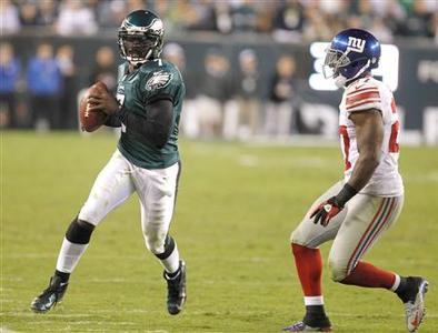 Philadelphia Eagles quarterback Michael Vick scrambles for a gain as the New York Giants safety Stevie Brown (R) runs him out of bounds during the fourth quarter of their NFL football game in Philadelphia, Pennsylvania, September 30, 2012. REUTERS/Tim Shaffer
