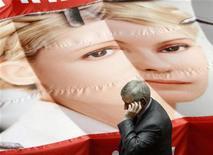 """Депутат оппозиционной партии экс-премьера Украины Юлии Тимошенко разговаривает по мобильному телефону, проходя мимо развернутого в зале заседаний парламента полотна с изображением Тимошенко, 25 апреля 2012 года. Отбывающая семилетнее заключение лидер украинской оппозиции, экс-премьер Юлия Тимошенко призвала граждан на предстоящих 28 октября парламентских выборах """"восстать"""" и сменить действующую власть. REUTERS/Anatolii Stepanov"""