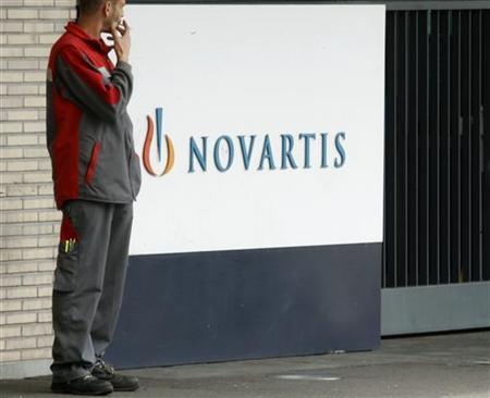 An employee smokes a cigarette beside the logo of Swiss drugmaker Novartis AG in front of a plant in Basel October 25, 2011. REUTERS/Arnd Wiegmann