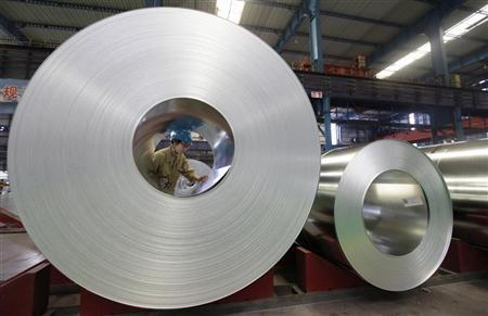 An employee checks on a steel product at a steel production factory in Wuhan, Hubei province, August 2, 2012.REUTERS/Stringer