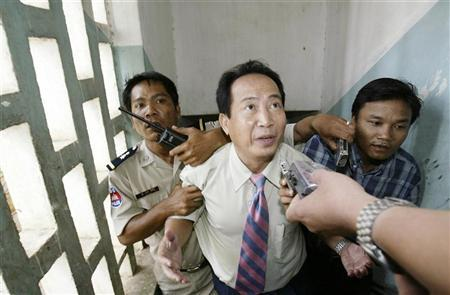 A Cambodian radio station director Mam Sonando (C) speaks to the press while being escorted by military police at Phnom Penh Municipality Court in Phnom Penh October 11, 2005.
