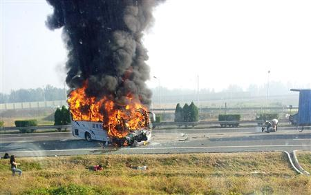 A tourist bus, seen through the window of a vehicle, catches fire after crashing with a truck on the Beijing-Tianjin-Tanggu Expressway in Tianjin October 1, 2012. According to local reports, the incident killed six, including five Germans and injured 14. REUTERS/Peng Jianfeng