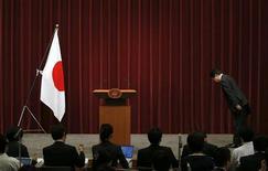 Японский премьер Ёсихико Нода кланяется национальному флагу во время пресс-конференции в Токио, 1 октября 2012 года. Премьер-министр Японии Ёсихико Нода в понедельник назначил нового министра финансов, который, как ожидается, поддержит бюджетные реформы и интервенцию на валютный рынок в составе нового кабинета, реформируемого в преддверии выборов. REUTERS/Toru Hanai