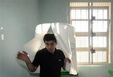 Заключенный покидает кабинку для голосования на избирательном участке в тюрьме в Тбилиси 1 октября 2012 года. В Грузии в понедельник проходят парламентские выборы, которые глава государства Михаил Саакашвили расценил как экзамен на популярность действующей власти, оказавшейся в фокусе скандала вокруг насилия над людьми в тюрьмах. REUTERS/Irakli Gedenidze