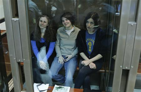 Members of the female punk band ''Pussy Riot'' (L-R) Maria Alyokhina, Yekaterina Samutsevich and Nadezhda Tolokonnikova sit in a glass-walled cage before a court hearing in Moscow, October 1, 2012. REUTERS/Maxim Shemetov