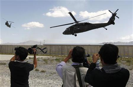 Afghan journalists film U.S. helicopters taking off after a ceremony handing over the Bagram prison to Afghan authorities, at the U.S. airbase in Bagram, north of Kabul September 10, 2012. REUTERS/Omar Sobhani