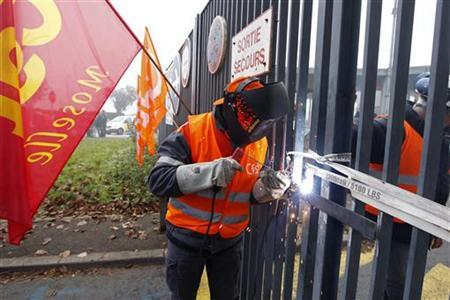 Employees of ArcelorMittal solder the gates of the local headquarters of the company as they demonstrate against the closure of blast furnaces at the Florange site, in Florange, October 1, 2012. REUTERS/Vincent Kessler