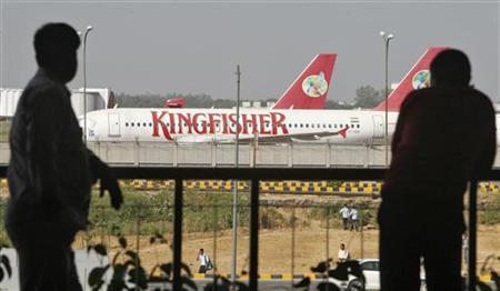 People are silhouetted as Kingfisher Airlines' aircrafts are seen parked at an airport in New Delhi October 1, 2012. REUTERS/Mansi Thapliyal