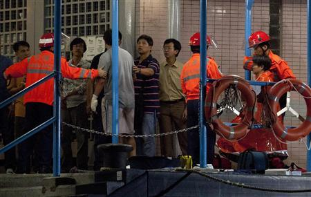 Two survivors, accompanied by rescuers, are taken onto shore after a collision involving two vessels in Hong Kong October 1, 2012. REUTERS/Tyrone Siu