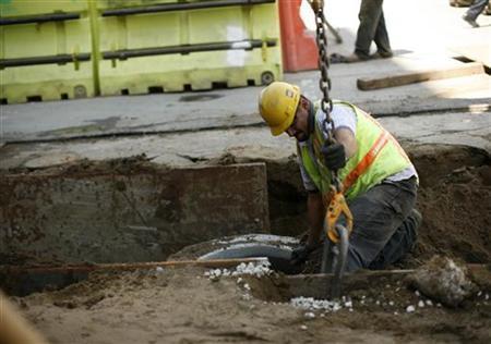 A worker handles equipment at a construction site in San Francisco, California September 1, 2011. REUTERS/Robert Galbraith