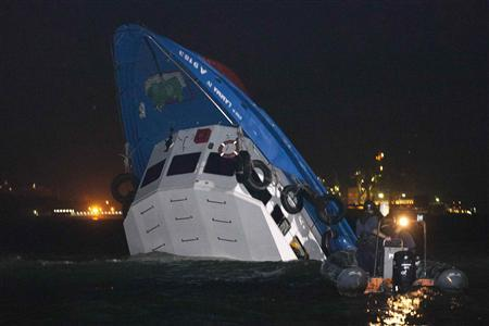 Rescuers approach a partially-submerged boat after two vessels collided in Hong Kong October 1, 2012. A major rescue is underway in the waters near Yung Shue Wan on Hong Kong's Lamma island following a collision involving two vessels in the evening, government radio reported on Monday. Police say there were about 100 people onboard both vessels, with many of them in the water. REUTERS/Tyrone Siu