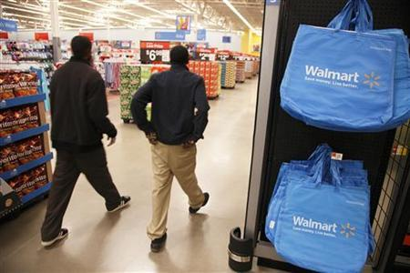Workers walk through a new Wal-Mart store in Chicago, January 24, 2012. The store will open on January 25, and it will be Wal-Mart's largest outlet in Chicago. REUTERS/John Gress