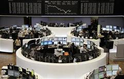 Traders are pictured at their desks in front of the DAX board at the Frankfurt stock exchange September 28, 2012. REUTERS/Remote/Marte Kiessling