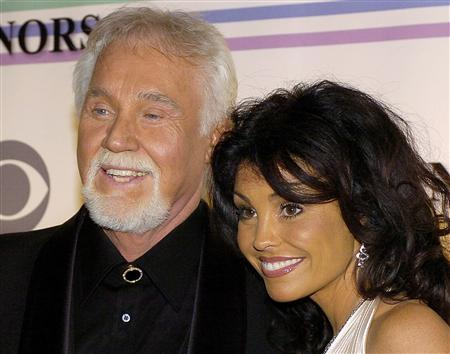 Country singer Kenny Rogers and his wife Wanda pose for photographers as the arrive at the Kennedy Center for the 29th Annual Gala in Washington in this file photo taken December 3, 2006. Rogers offers a revealing look into his life and five-decade-long musical career in ''Luck or Something Like It,'' his memoir that will be released on Tuesday. REUTERS/Mike Theiler