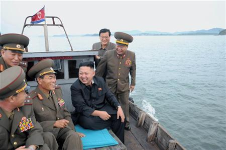 North Korean leader Kim Jong-Un (C) sits in a wooden boat with other soldiers as he visits military units on islands in the most southwest of Pyongyang in this picture released by the North's official KCNA news agency in Pyongyang August 19, 2012. REUTERS/KCNA