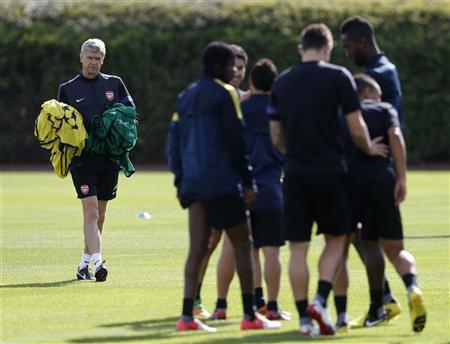 Arsenal manager Arsene Wenger carries the players bibs during a team training session in London Colney, north of London September 17, 2012. REUTERS/Eddie Keogh